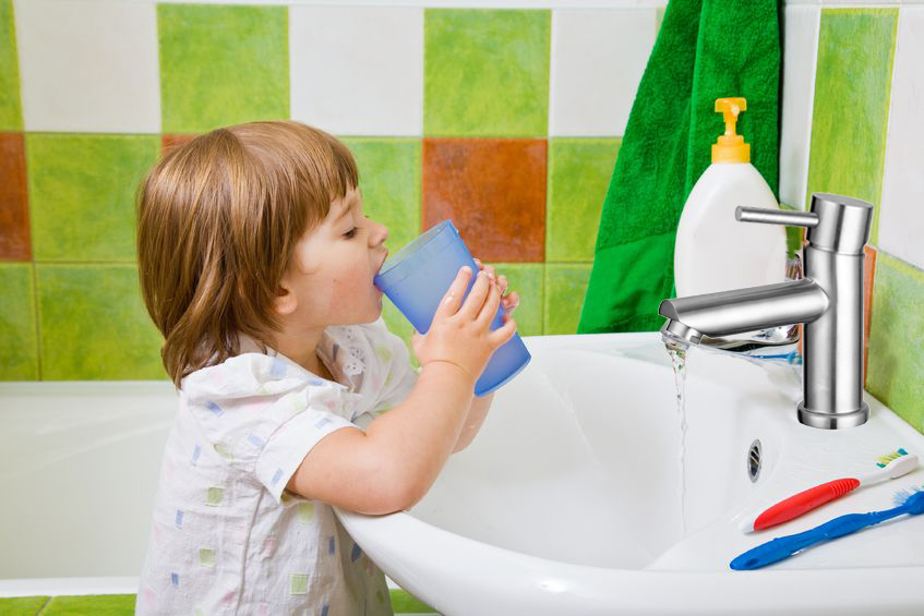 personal hygiene. the little girl rinses a mouth after toothbrushing.